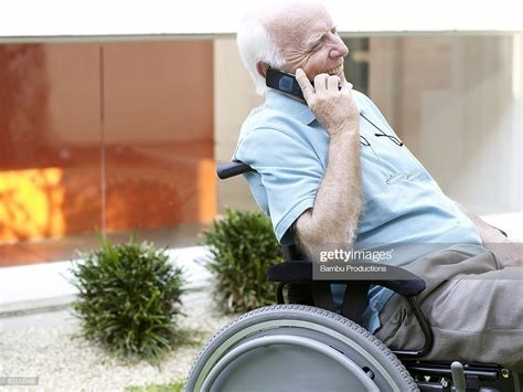 Homebound Friends Man on a Wheelchair talking on his phone with volunteer.