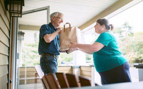 Homebound Friends Man Receiving Groceries from Volunteer.